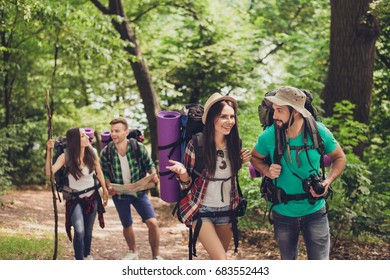 Two cheerful couples are clmbing up the hill, talking, having fun together, wearing comfortable outfits for hiking, sneakers, hats, have backpacks, camers, map