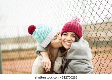 Two cheerful cute teenage girls hugging, one girl kissing her best female friend outdoors in winter. Two young women in knitted beanies and coats. No retouch.