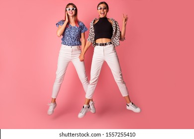 Two cheerful excited young women jumping and having fun together over pink background