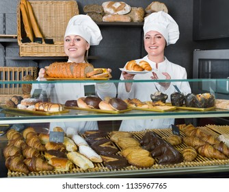 Two cheerful  female cooks demonstrating and selling pastry in the cafe counter