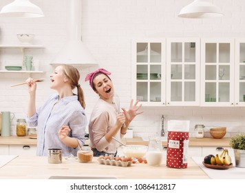 Two cheerful friends cook together. Friends Chef Cook Cooking Concept.