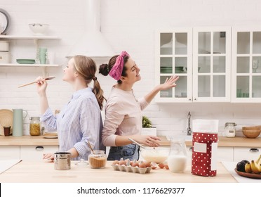 Two cheerful friends cook together desserts and sing.