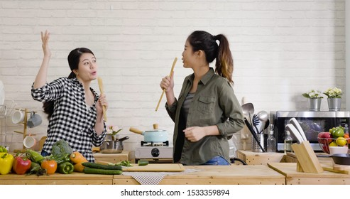 Two cheerful friends cook together and sing with spatulas as microphone. young japanese girls dancing and having fun in kitchen. ladies roommate making salad for healthy meal on weekend day time.