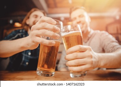 Two cheerful friends sit in sports bar and clink glasses with beer. Friendship concept, hockey fans.