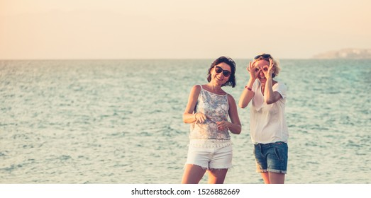 Two cheerful girlfriends posing and laughing from tomfoolery against the backdrop of the sea. Rest and travel. Place for text
