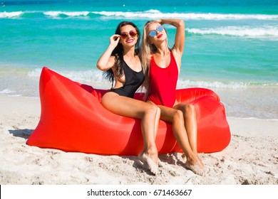 Two cheerful girls, blonde and brunette sitting on the beach on an inflatable air sofa, laughing, having fun, red, black sexy swimsuits, tanned bodies, long hair, relaxing, tropical island, sunglasses