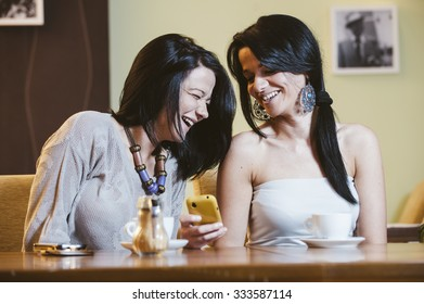two cheerful girls drinking coffee