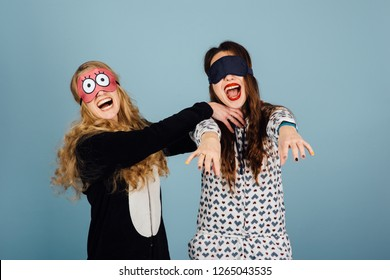 two cheerful girls in masks for sleeping have fun playing sleepwalking