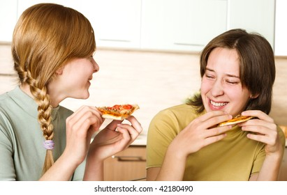Two cheerful girls with pizza