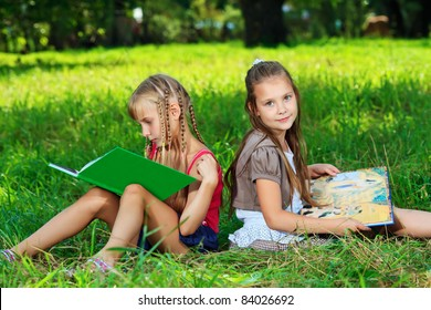 Two cheerful girls reading books outdoors.