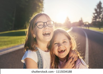 Two cheerful girls standing on the road, hugging and smiling against the sunset. Young generation. Girls without front teeth.