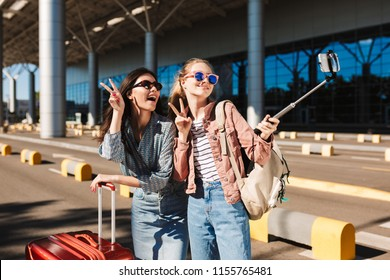 Two cheerful girls in sunglasses happily showing two fingers gesture taking photo on cellphone together with suitcase and backpack on shoulder outdoor near airport
