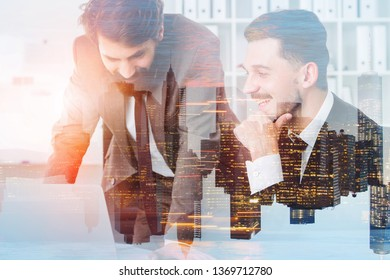 Two cheerful handsome businessmen working with laptop in modern office with double exposure of night cityscape. Concept of management. Toned image