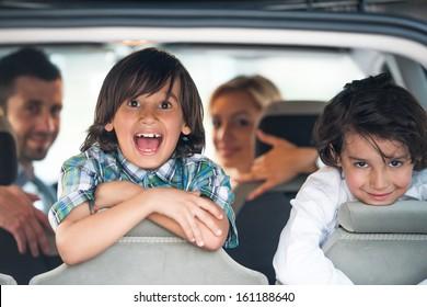 Duas crianças alegres em um banco traseiro de carro