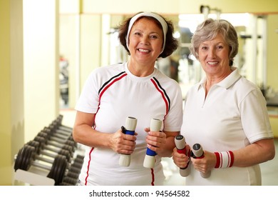 Two cheerful ladies looking at camera holding dumbbells