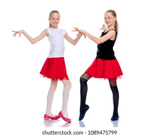 Two cheerful little girls are dancing in the studio on a white background. The concept of a children's dance school, happy people. Isolated.
