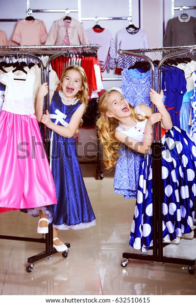 Two cheerful little girls enjoy shopping. Kid's fashion. Seasonal sale, shopping.