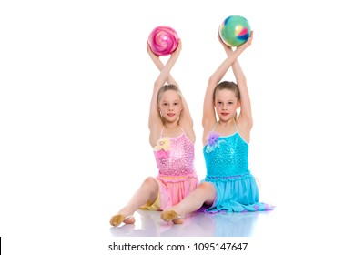 Two cheerful little girls gymnasts in competitions, perform exercises with the ball. The concept of children's sports, fitness, healthy lifestyle. Isolated on white background.
