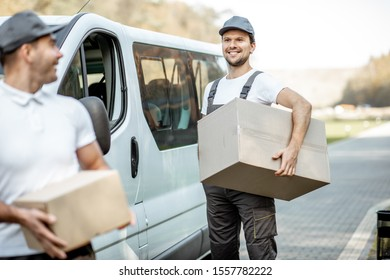 Two cheerful male couriers in uniform delivering goods by cargo van vehicle, unloading cardboard parcels from a car outdoors