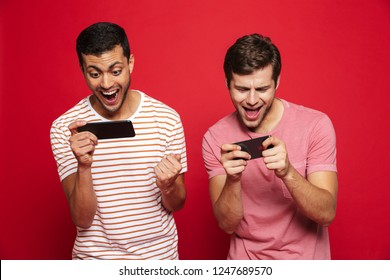 Two cheerful men friends standing isolated over red background, playing games on mobile phones