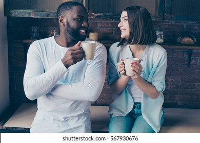 two cheerful mixed race people drink tea and talk in  kitchen.   Handsome afro american guy together with his  beautiful caucasian girl.