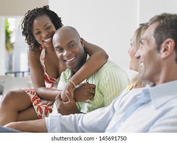 Two cheerful multiethnic couple chatting at home
