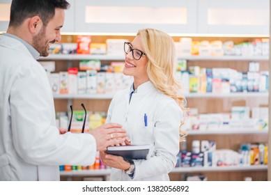 Two cheerful pharmacists talking in hospital pharmacy.