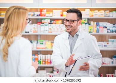 Two cheerful pharmacists working on medicines inventory at hospital pharmacy.