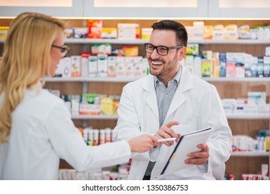 Two cheerful pharmacists working together.