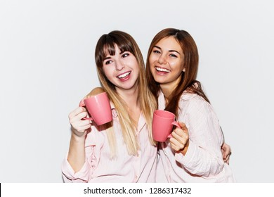Two cheerful pretty  friends in pink pajamas  with cup of tea posing on white background. Flash portrait.