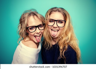 Two cheerful pretty girls in glasses stick out their tongue. Blue background. Beauty, fashion. Optics, eyewear.