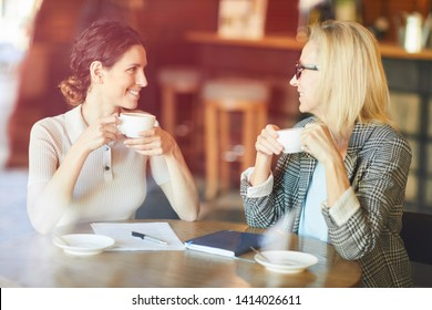 Two cheerful pretty women having coffee in cafe while discussing points of new project or new working ideas