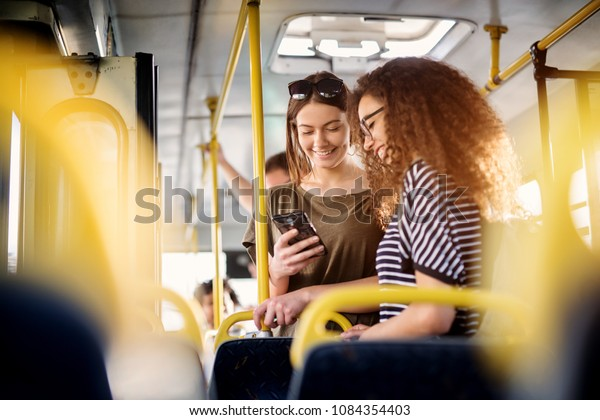 Two cheerful pretty young women are standing in a bus and looking at the phone and smiling while waiting for a bus to take them to their destination.