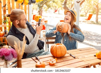 Two cheerful and rejoiced young adult friends making decoration for halloween, holding carved pumpkin in hands, taking self portrait on modern smartphone, sitting outdoor