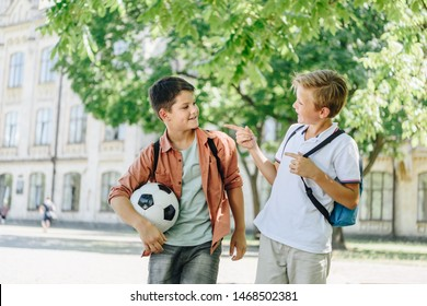 two cheerful schoolboys with backpacks talking while walking in green park