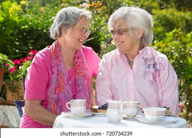 Two cheerful senior women chatting while having tea at table in garden