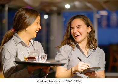 Two cheerful waitresses take a customer's order in the hotel restaurant. Evening time. Laughing girls. The concept of service.
