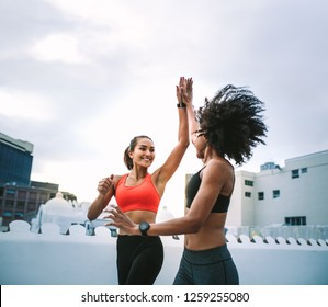 Two cheerful women in fitness wear giving high five while running on the terrace. Women athletes doing fitness training on the rooftop giving high five.