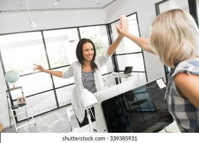 Two cheerful women in office giving high five