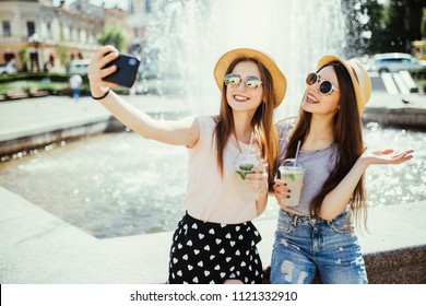 Two cheerful women pose against fountain with smoothie, make selfie on modern mobile phone or talk online on video call, share their impressions about resort abroad