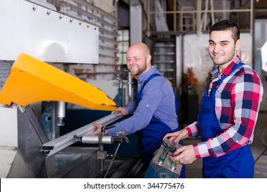 Two cheerful workers in uniform working on a machine in PVC shop and smiling