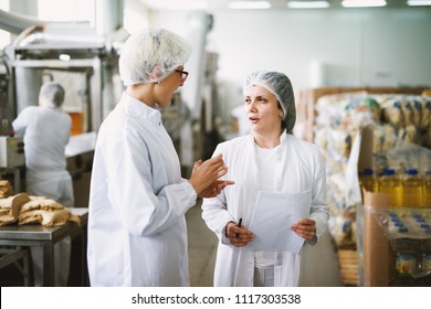 Two cheerful workers in white sterile cloths are standing in a food factory and talking while one of them is holding statistic papers.