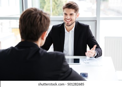 Two cheerful young businessmen using tablet and working together on business meeting in office