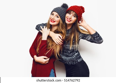 Two  cheerful young friends in perfect mood having time together on white isolate background. Wearing   trendy winter sweater and knitted red and grey hat . Positive and friendship concept.