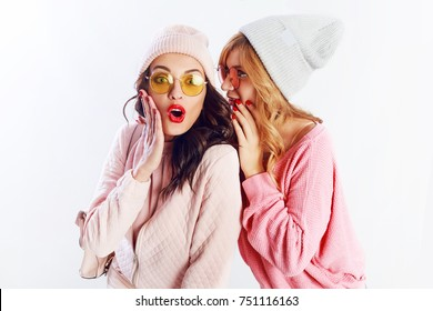 Two cheerful young friends in perfect mood having time together on white isolate background. Positive girls share secrets with each other wearing pink cozy sweaters and pullover.