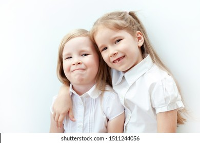 Two cheerful young girls, children hugging each other hand over a shoulder on white background. Cheerful sisters, close friends, happy childhood, happiness concept. One girl without a front tooth