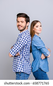 Two cheerful young lovers are looking at the camera and smile, standing back to back, wearing casual clothes, with crossed hands on the pure background
