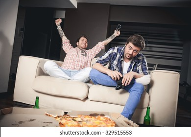 Two cheerful young men playing video games while sitting on sofa