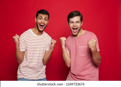 Two cheerful young men standing isolated over red background, celebrating success