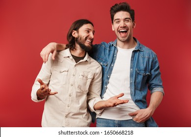 Two cheerful young men wearing casual clothes standing isolated over red background, laughing